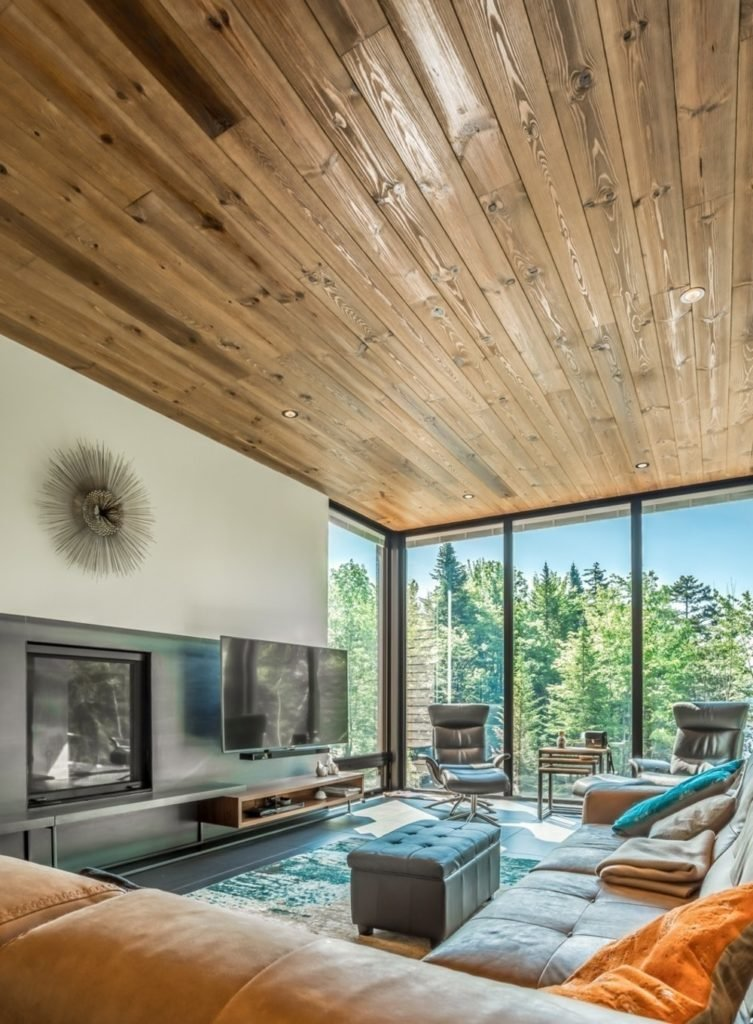Cozy living room with panoramic windows and wood plank ceiling fitted with recessed lights. It has leather seats and a fireplace next to the flat panel TV mounted above the floating shelf.