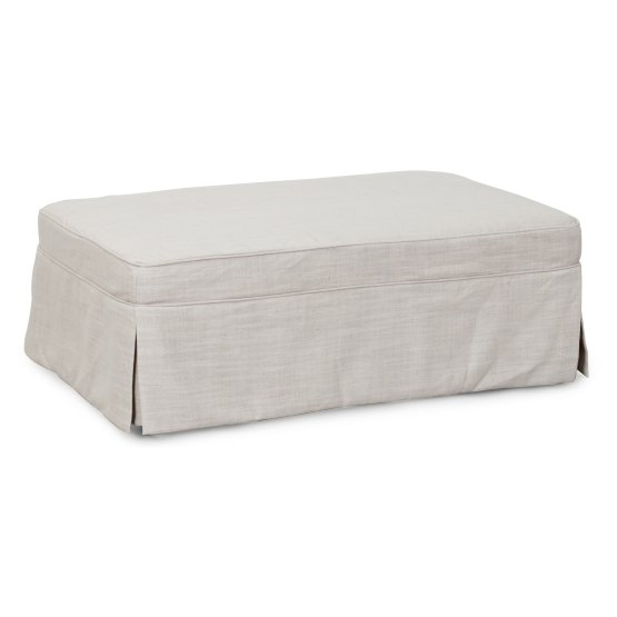 An ottoman with slipcovered sides.
