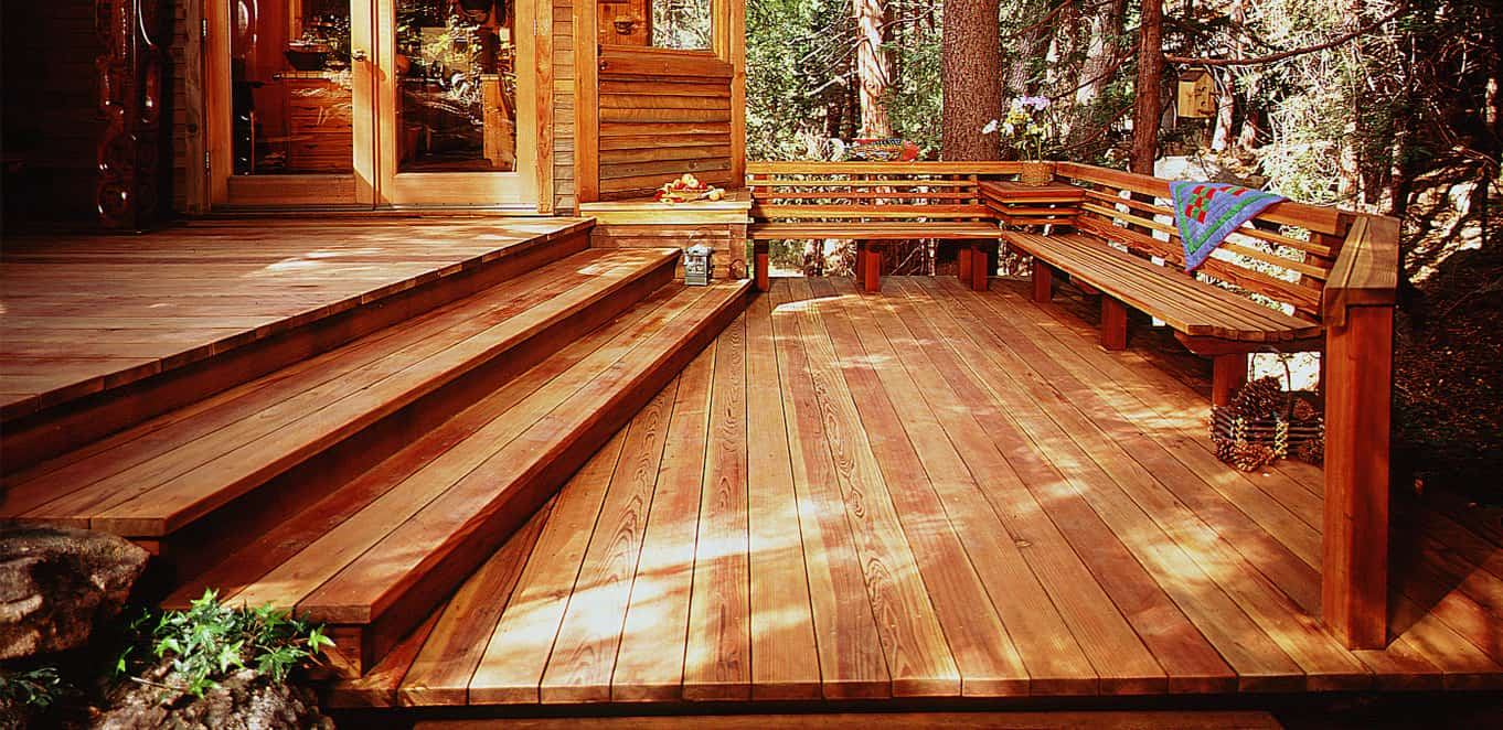 This rustic deck offers a bench seating surrounded by trees and other greenery.