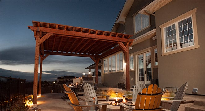 Redwood lumber pergola at night next to fire pit