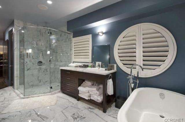 The Bathroom Features A Contemporary Style And A Soaking Tub Together With  A Walk In Shower.