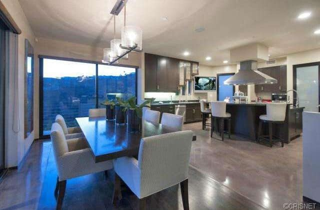 The kitchen offers a dine-in kitchen featuring a rectangle 6-seats table set lighted by pendant and recessed lights.