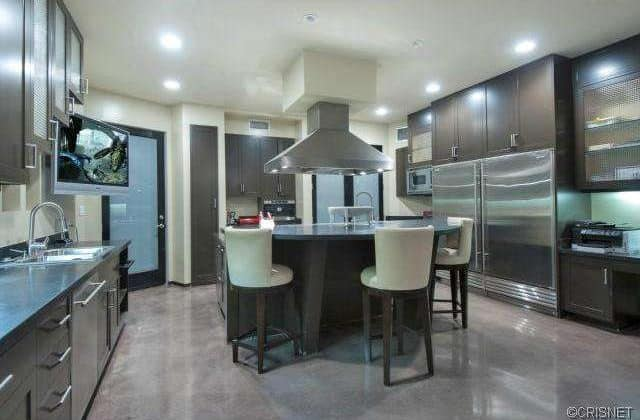 The kitchen also offers a round dine-in table set. Stainless steel appliances and counter fits well with the kitchen's style while TV provides entertainment.
