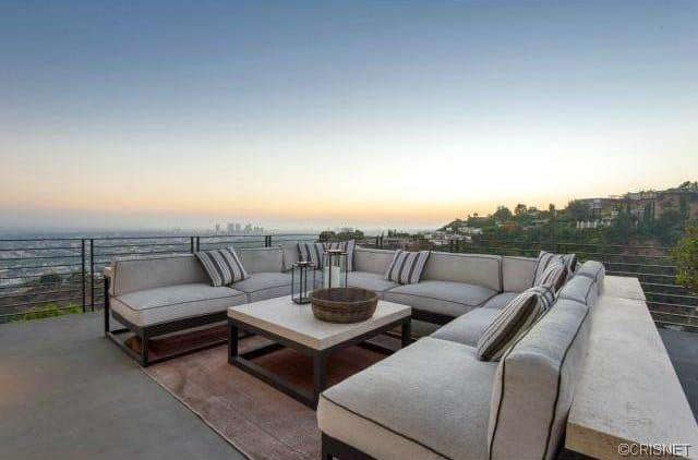 This luxurious patio area offers a comfortable and stylish U-shaped sofa set with a rug and a center table overlooking the gorgeous city.