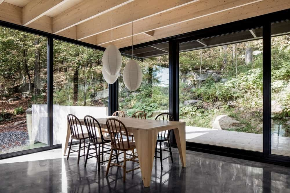 You can feel you're one with nature in this fully glazed dining room. It includes a wooden table with matching chairs that complements with the wood beam ceiling.