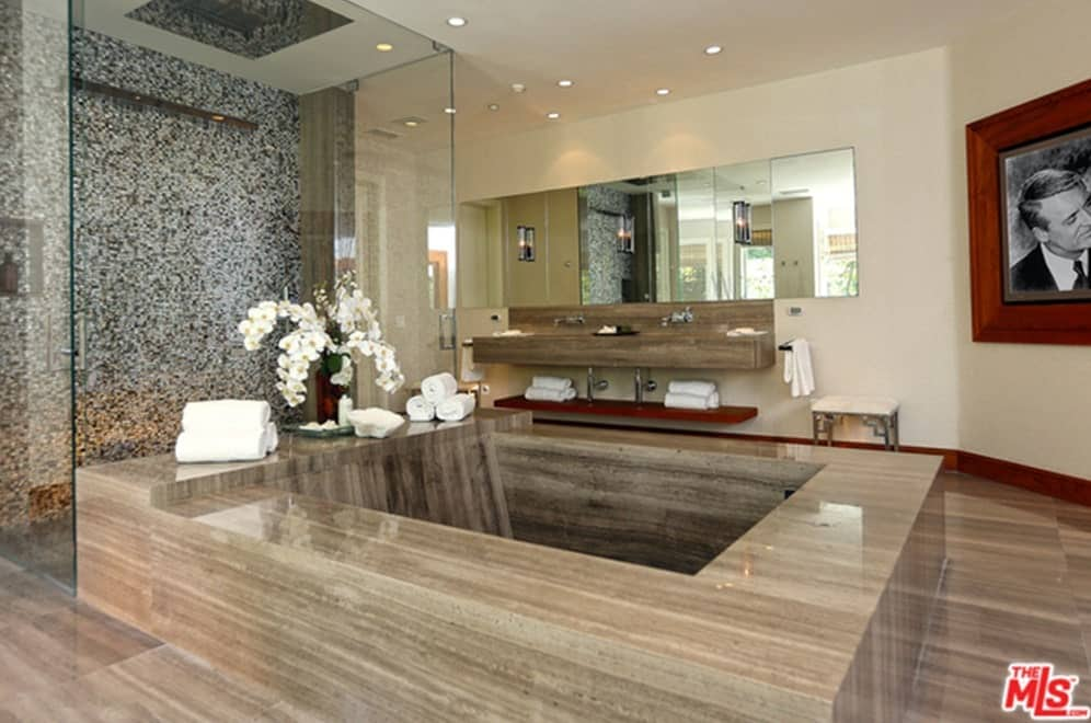 A primary bathroom with a stunning large bathtub, a stylish walk-in shower and a floating vanity double sink lighted by recessed ceiling lights.