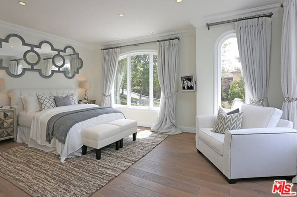 This master bedroom features white walls matching the white bed and large chair. The window curtains are white as well, matching the room's style.