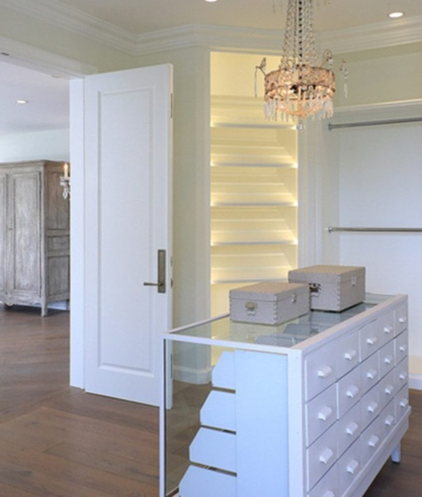 Spacious walk-in closet boast multiple cabinets and clothesline lighted by an elegant chandelier and recessed lights.