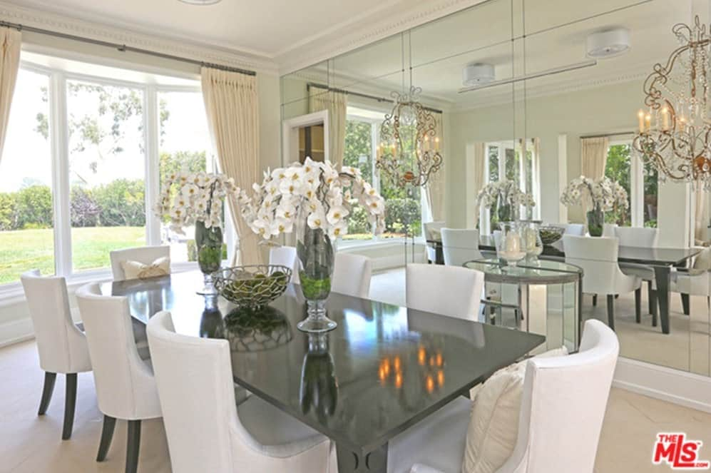 The dining room looks very elegant with its white set of chairs perfectly matches the white walls. Wide glass windows overlook outdoor views.