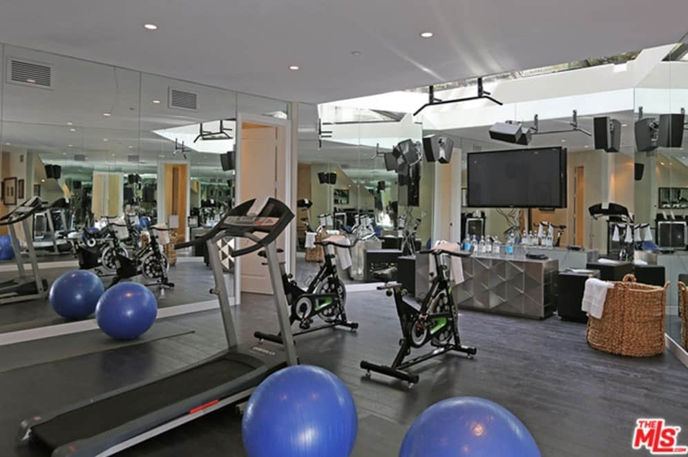 The mansion also includes a home gym with a hardwood flooring and recessed ceiling lights.