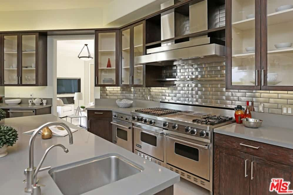 The kitchen boasts a traditional look featuring stainless steel appliances and multiple storage.