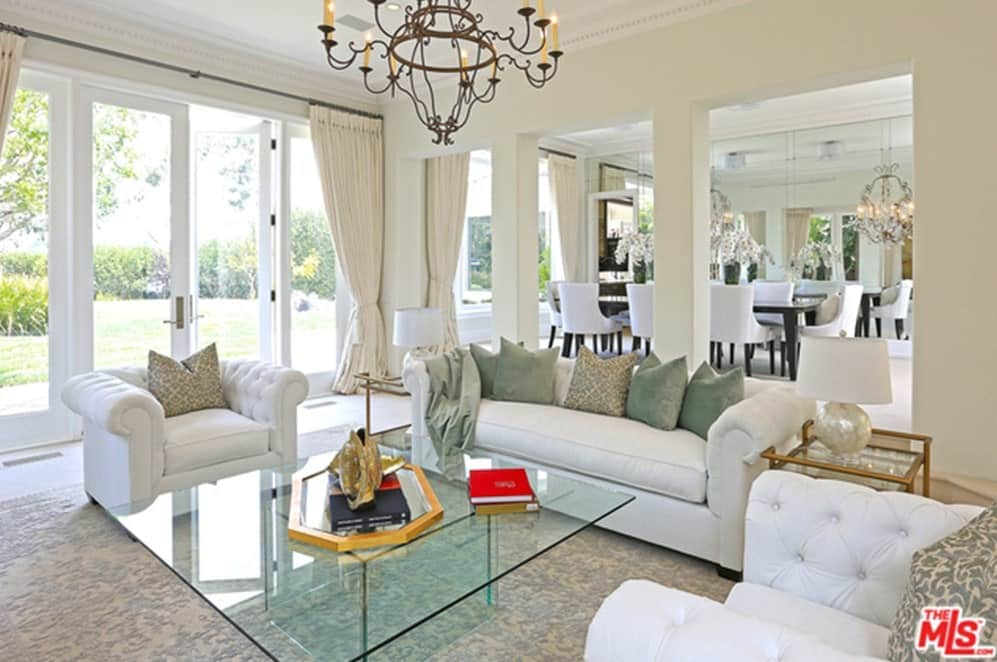 This living room is surrounded by white walls and ceiling lighted by a stunning chandelier. The glass top center table looks perfect together with the white sofa and chairs.