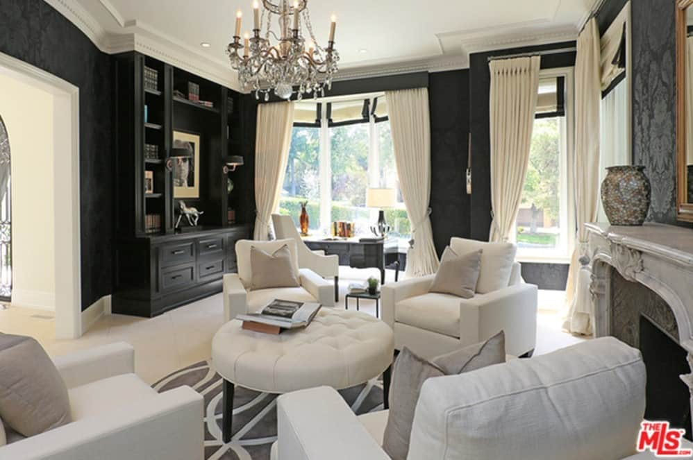 The mansion has a home office with black walls and white seating set in front of a fireplace. Grand chandelier brightens the room while glass windows lets sunlight through.