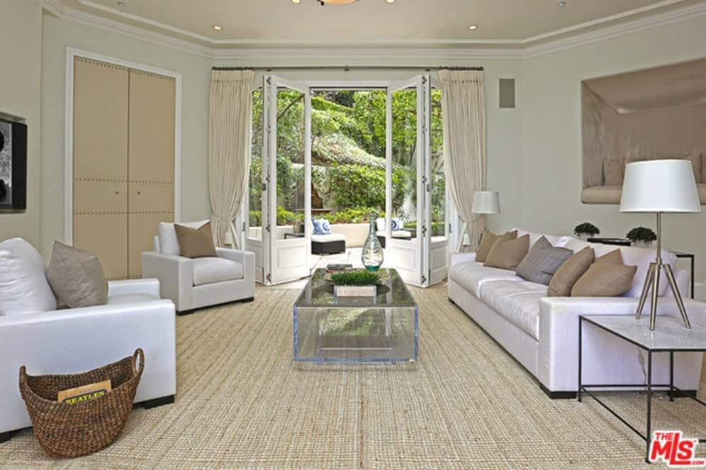 This living room features a nice set of sofa and chairs along with a glass center table. That doorway leads to the home's outdoor area.
