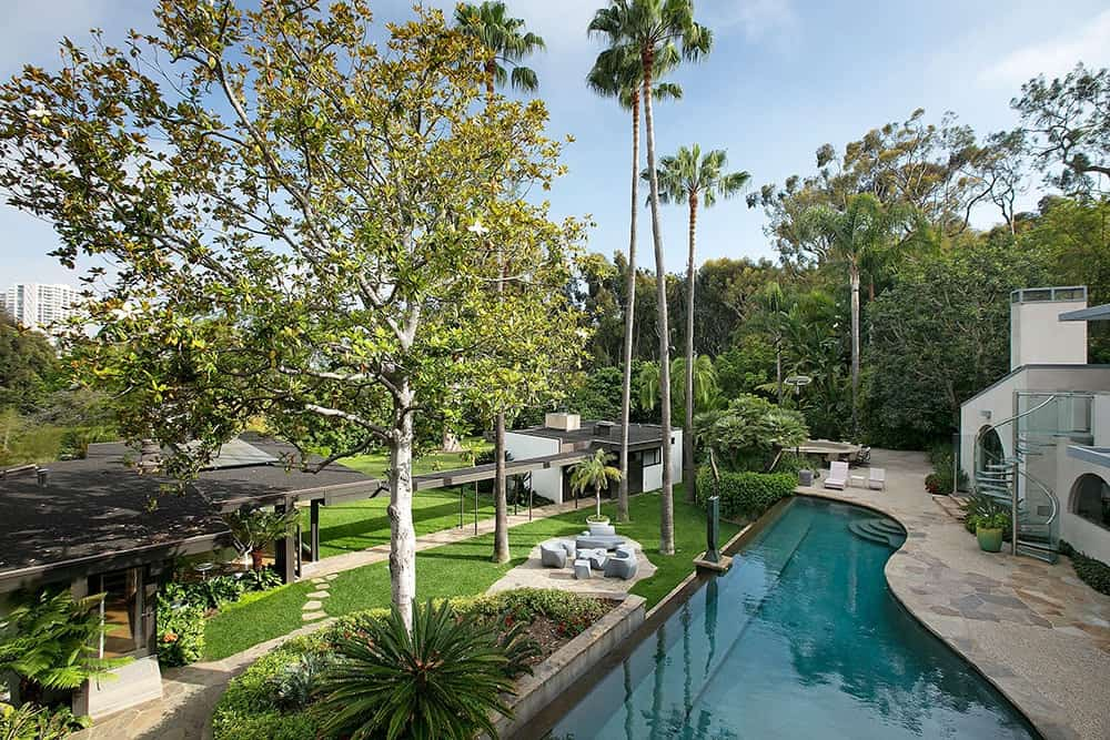 Another aerial view of the house showcasing the beautiful landscape, garden and custom pool.