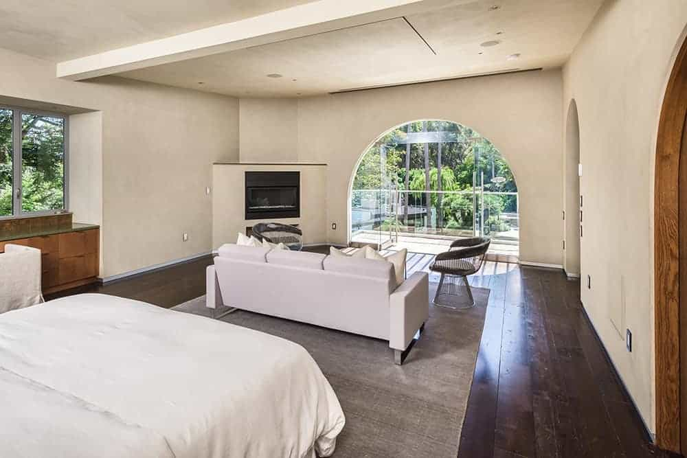 This primary bedroom features white walls and ceiling along with hardwood floors topped by a gray rug. It also has access to a private balcony.