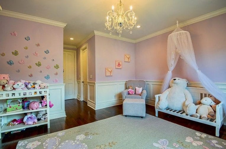 The kid's bedroom features a lavender walls and chandelier lighting. Customized rug fits well with the hardwood flooring.