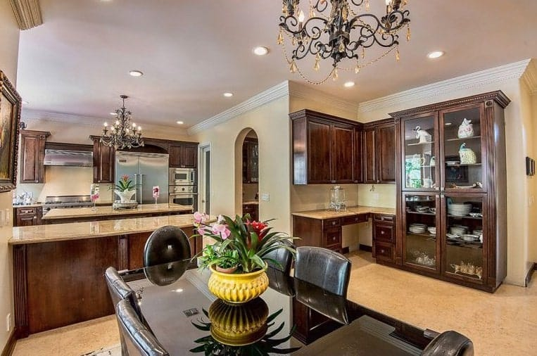 The kitchen overflows with elegance with its chandelier and recessed lights combination. Counters boast marble countertops while the dine-in table features a glass top.