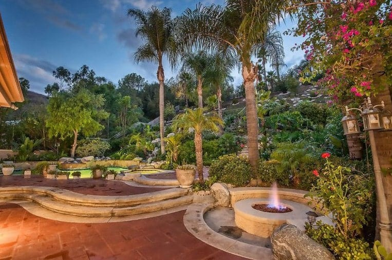 The mansion's backyard hides a lavish tropical view with fire pit and seating area combination.