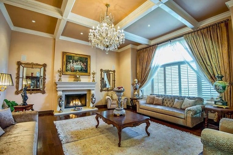 Luxury living room illuminated by a fancy chandelier that hung from the coffered ceiling along with natural light that flows through the louvered windows covered with sheer and gold draperies.