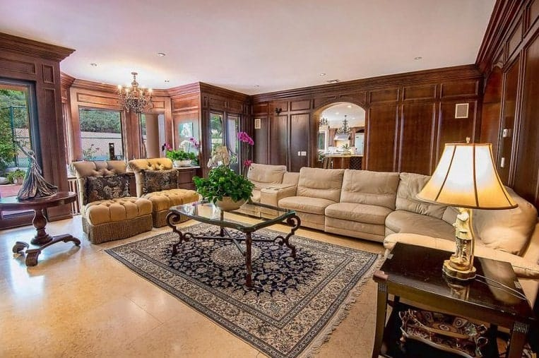 This living room boasts luxurious seats and a glass top center table set on a classy rug. The rustic shade surrounding the room looks elegant.