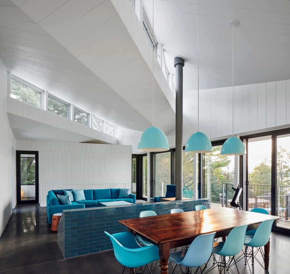 White shiplap walls and ceiling accented with a blue sectional, brick divider, sky blue pendant lights and dining chairs that surround a rectangle wooden table.