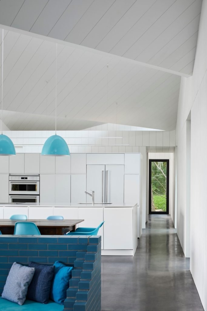 Cotemporary white eat-in kitchen accented with blue dome pendants that hung from shiplap ceiling and modern chairs surrounding the wooden dining table.