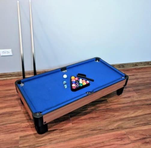 Blue, felt-covered mini pool table.