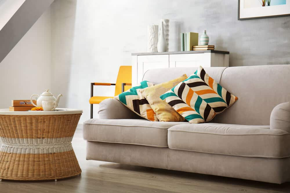Neutral-toned sofa with colorfully printed throw pillows.