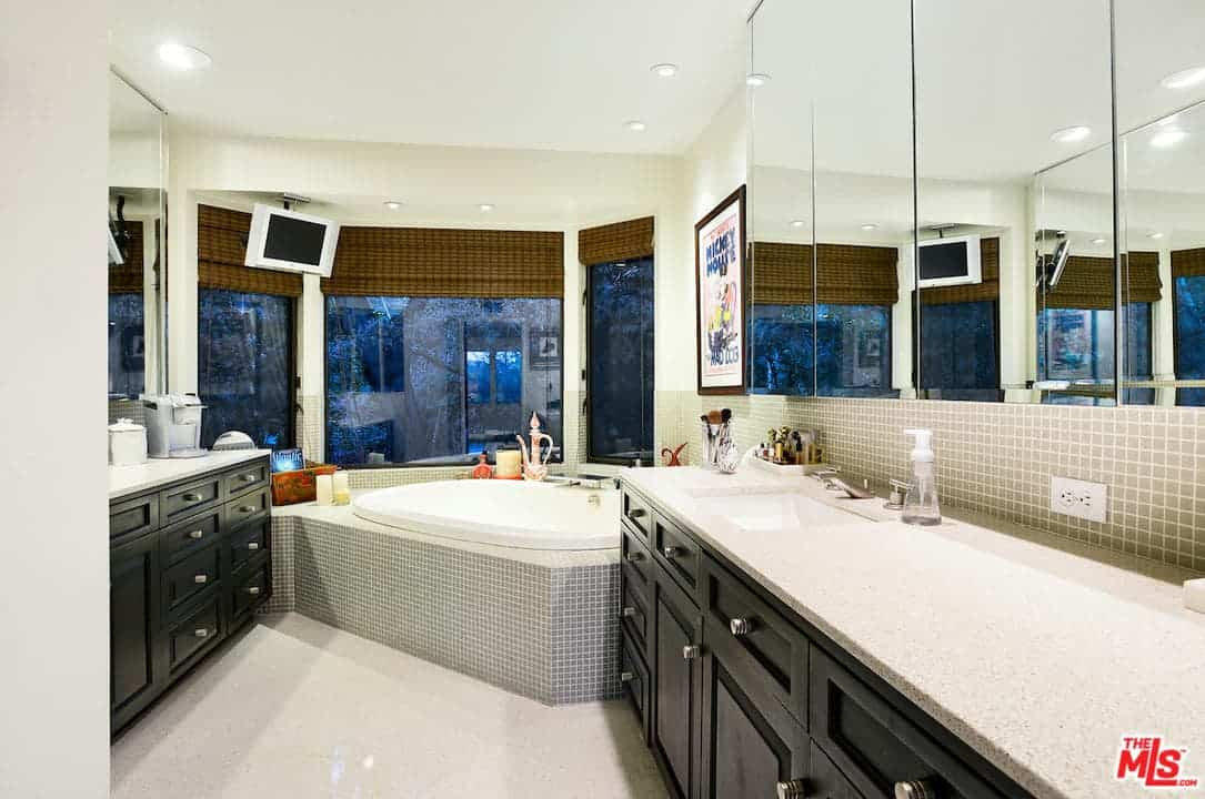 A luxurious bathroom features a grand soaking tub in front of a TV and clear glass windows.
