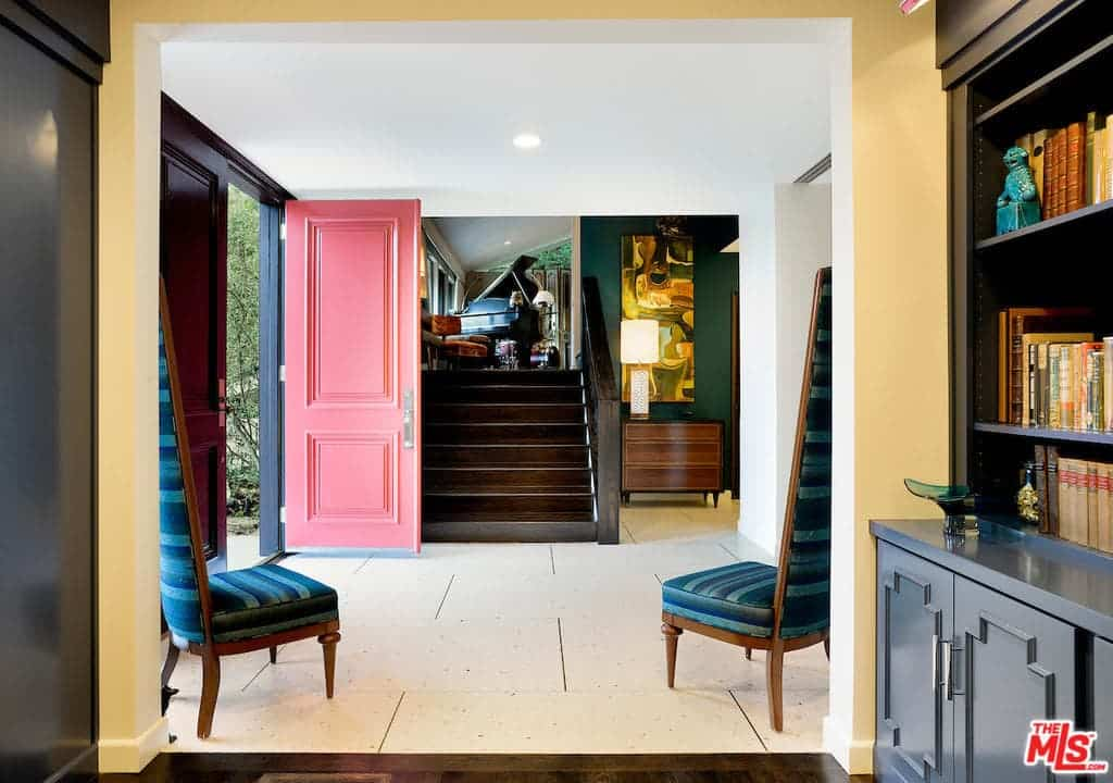 This country style foyer features a tiles flooring, green walls, pink door and a set of blue chairs with tall backrests.