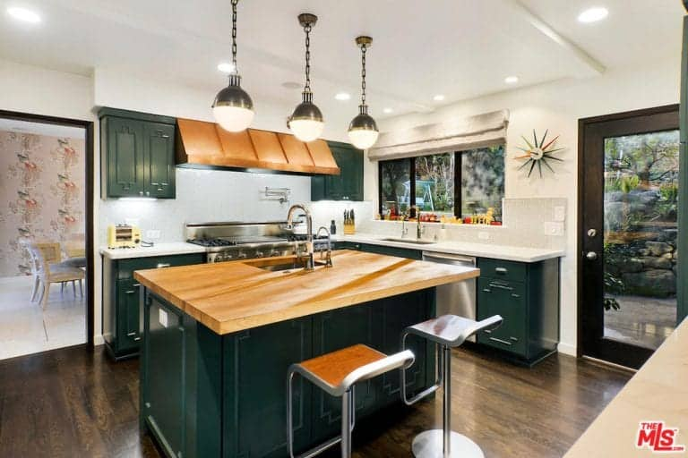 Country style kitchen with windows, glass door, green cabinetry, and a matching green base cabinet kitchen island with wood surface, sink. and a pair of bar stools.