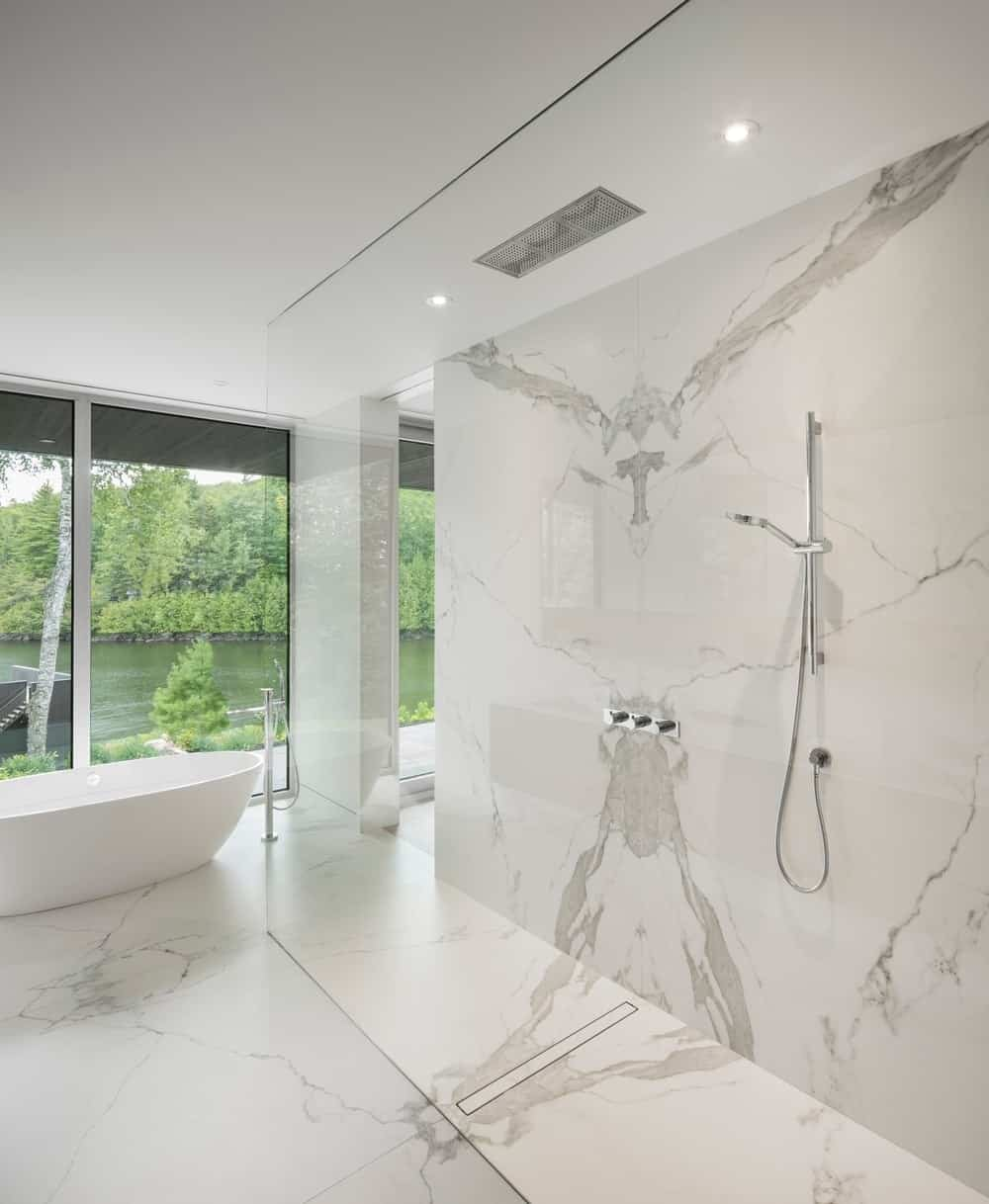 Primary bathroom boasts an open shower and freestanding tub along with white contemporary walls and glass windows. Photo Credit: Stephane Groleau