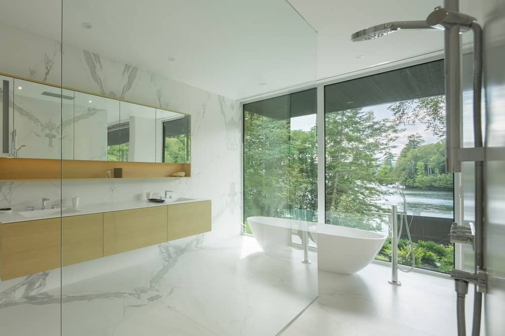 A glamorous bathroom with marble tiles floors and walls. There's an open shower and a freestanding tub near the glass window overlooking the beautiful river view surrounding the house.