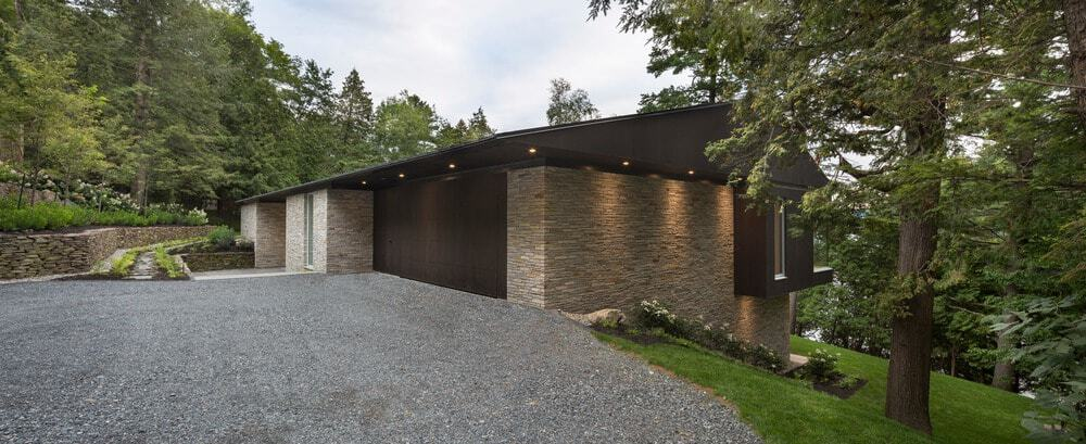 Spacious garage with a walkway is surrounded by the beautiful landscape. Photo Credit: Stephane Groleau