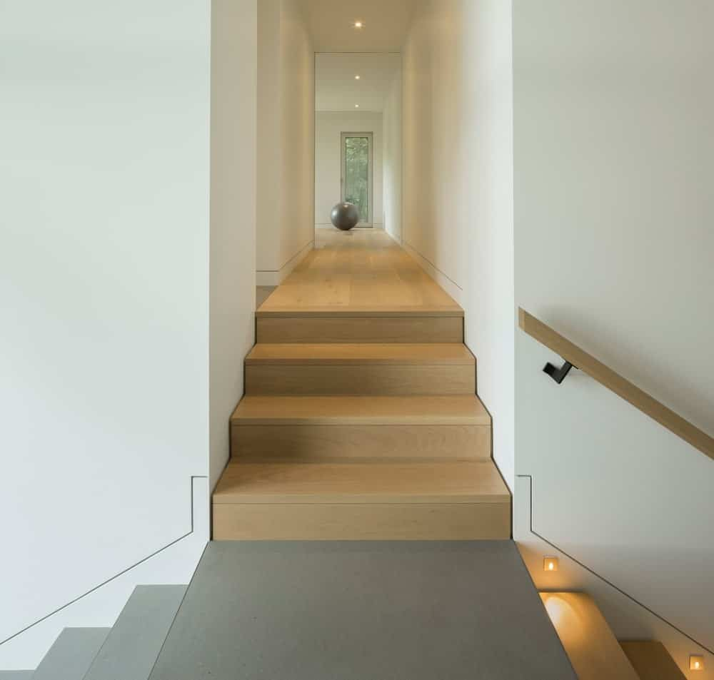 Staircase leading to hallway features white walls and hardwood flooring. Photo Credit: Stephane Groleau