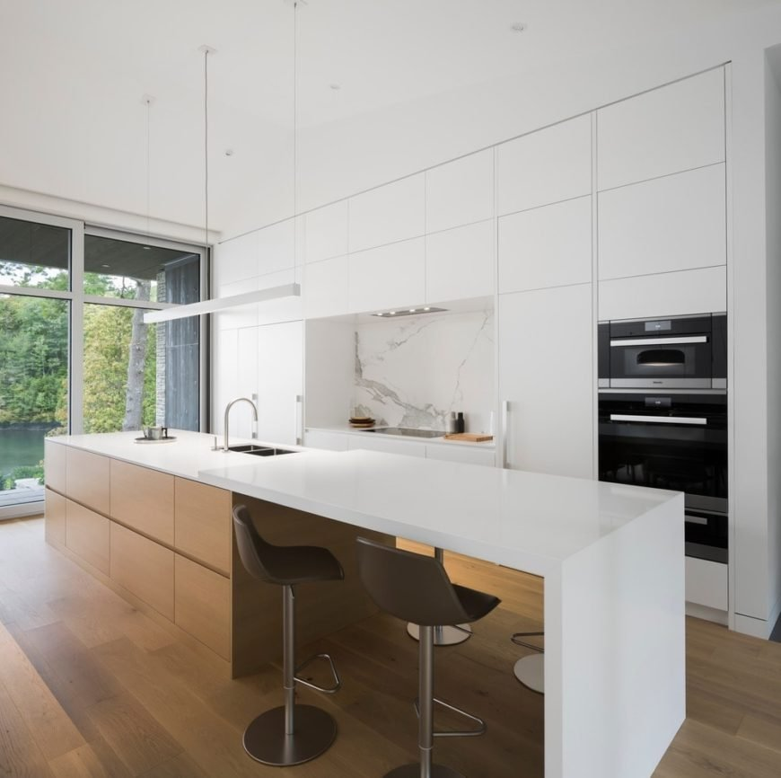 Sleek white kitchen includes wooden breakfast island topped with smooth white countertop, white marble backsplash, long linear lighting and a pair of stool bars.