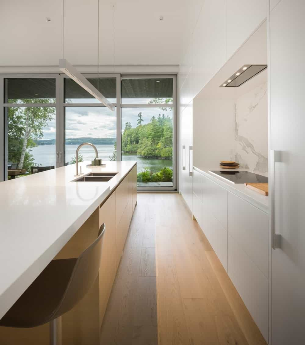 The kitchen boasts an elegant hardwood flooring and white countertop and walls. Photo Credit: Stephane Groleau