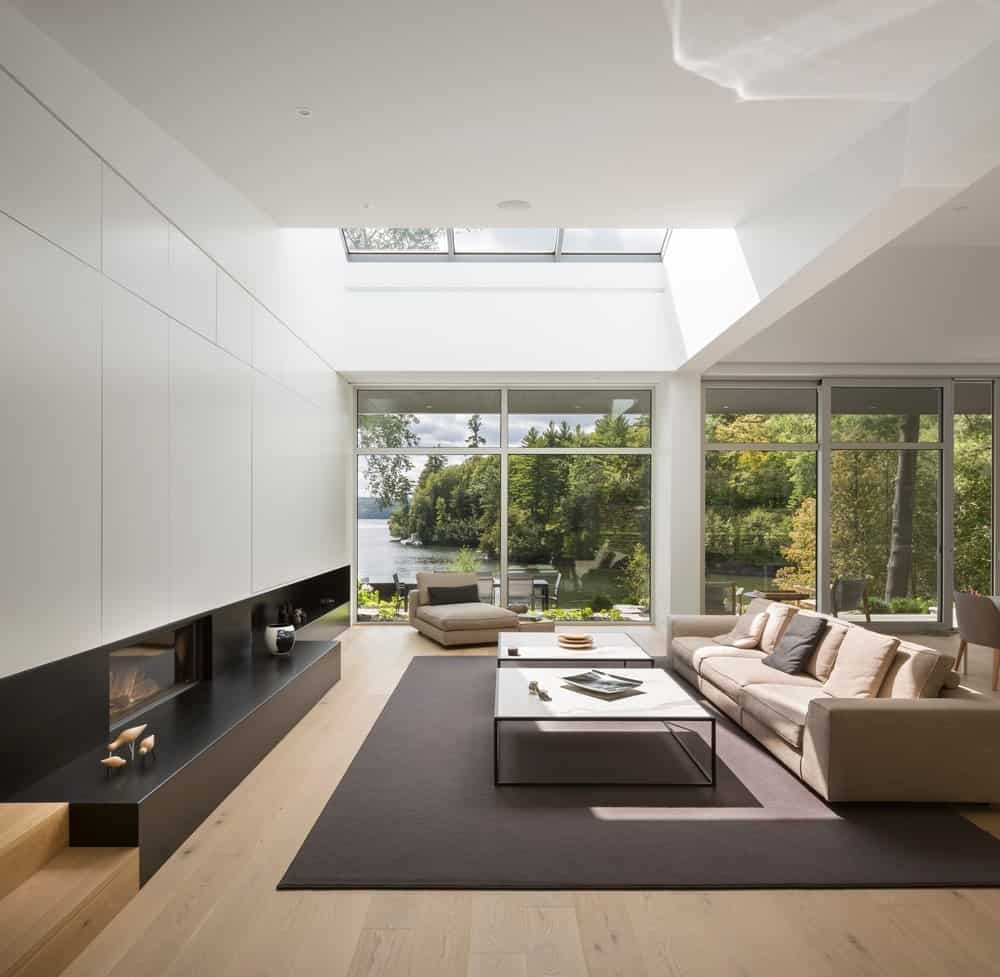 Contemporary great room with white walls and nice sofa set featuring a skylight ceiling and glass windows. Photo Credit: Stephane Groleau