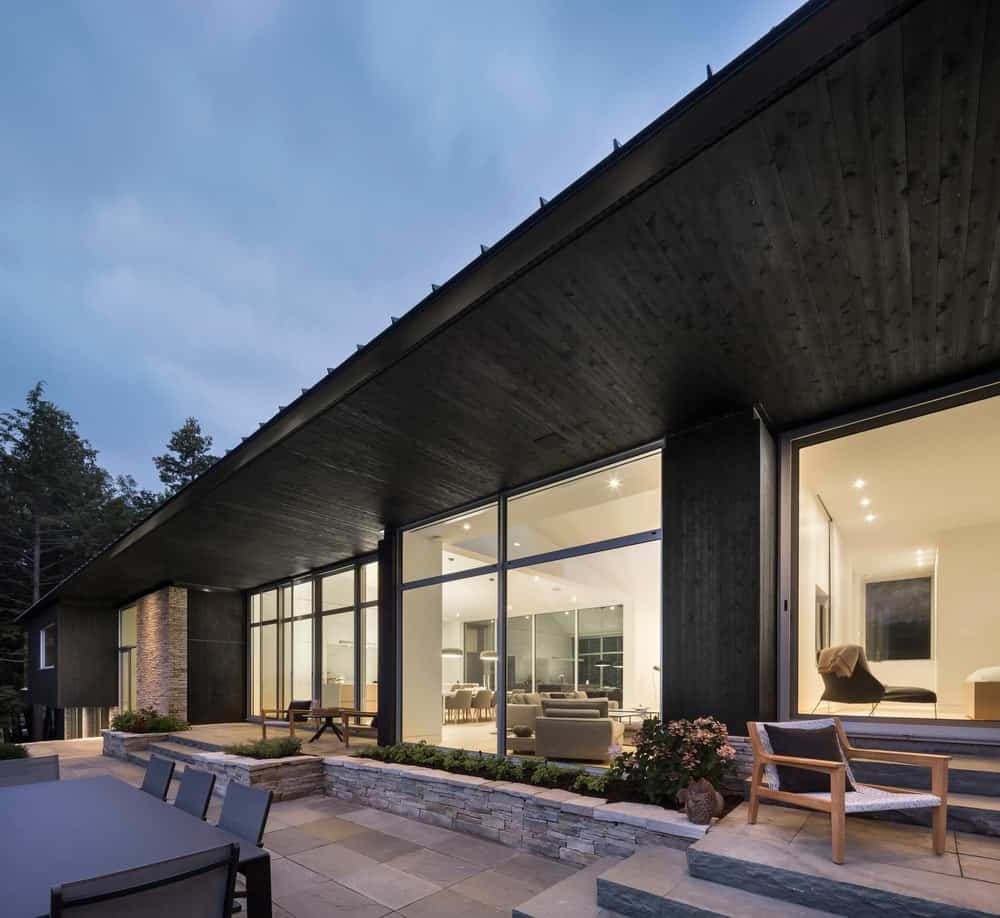 The house's contemporary black structure perfectly matches the beautiful outdoor patio. Photo Credit: Stephane Groleau