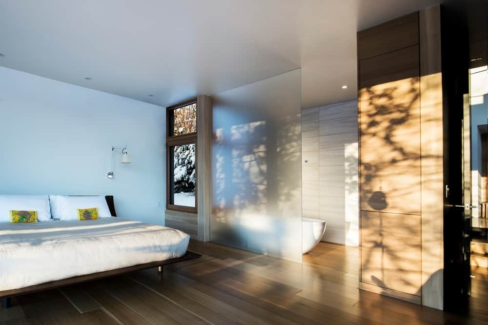 This modern master bedroom with a hardwood flooring also offers its own bathtub.