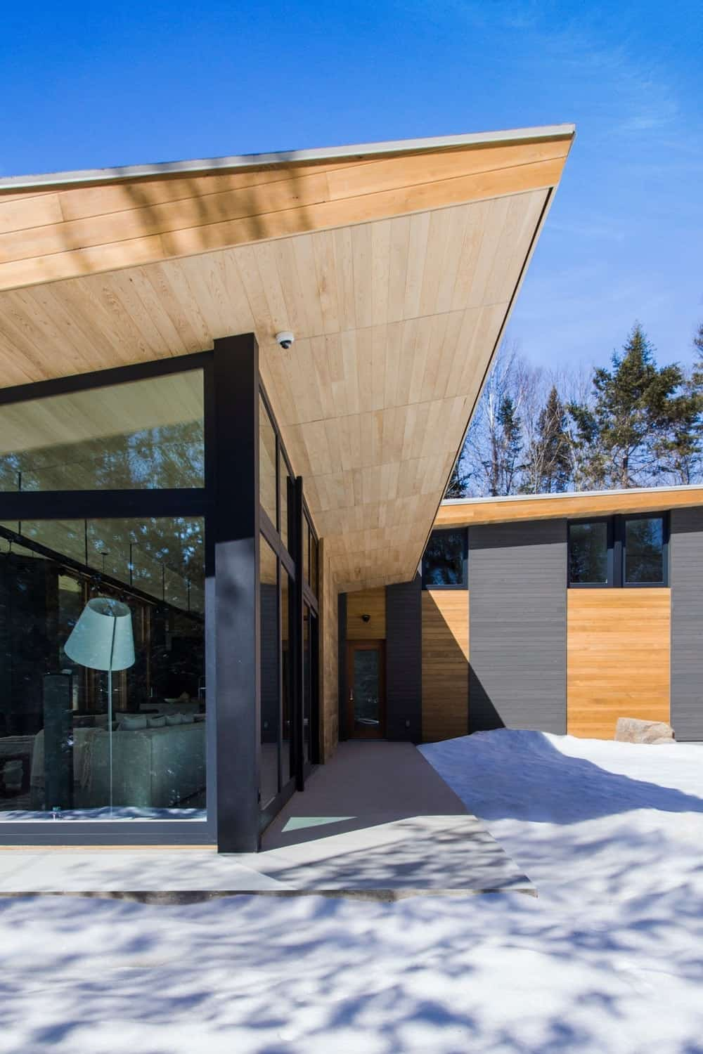 Another look of the house from outside showcasing the hardwood and glass architecture. Photo Credit: David Marien-Landry