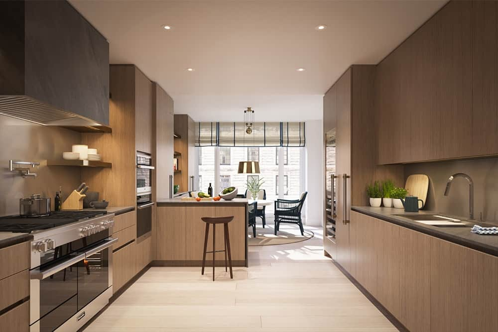 Spacious galley kitchen with tiny breakfast bar paired with a wooden bar stool, wood cabinets, gray countertops and backsplash illuminated by recessed lighting and natural light that comes from the glass walls of the dining area.