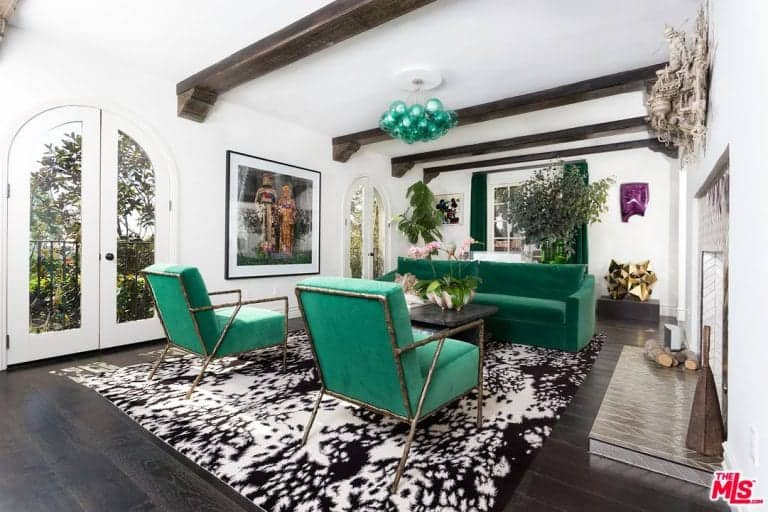 This Mediterranean home boasts a lovely formal living room featuring a green sofa set on top of a classy rug set on the hardwood flooring. The green sofa set matches the green curtains and ceiling lighting.