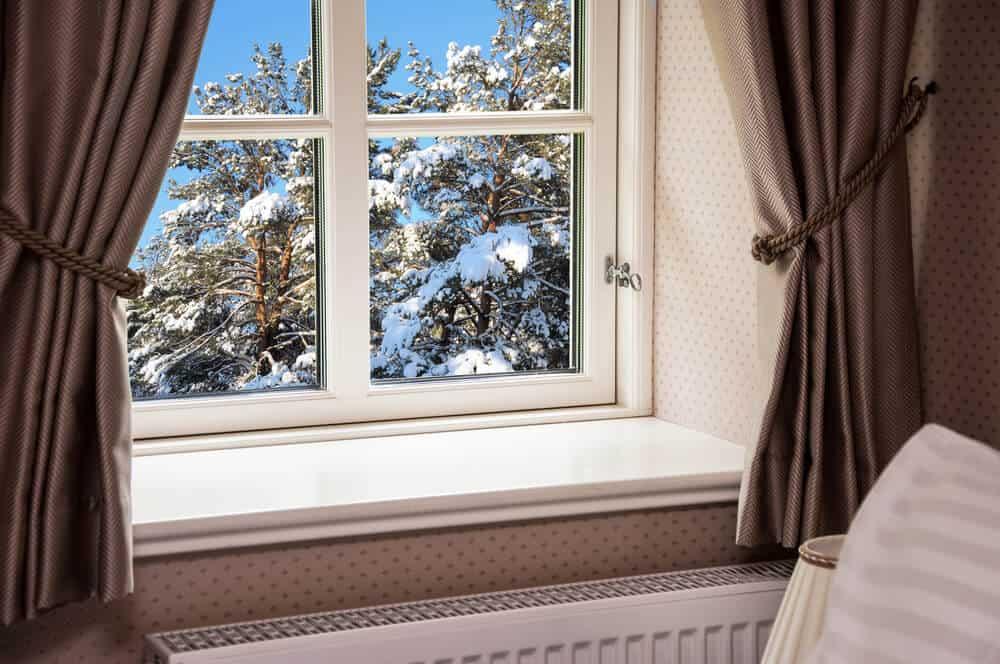 White-framed window with a dark brown velvet curtain.