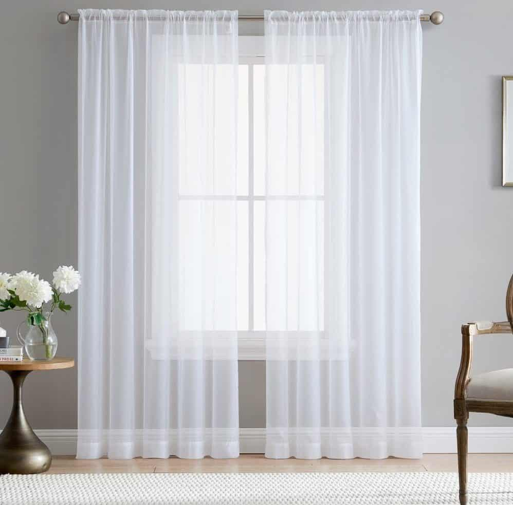 White, sheer window curtain that filters the flow of light.