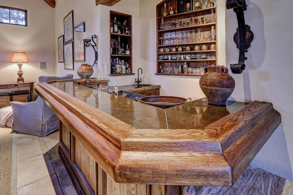 This bar features a bar made of hardwood set on the tiles flooring under the ceiling with beams.