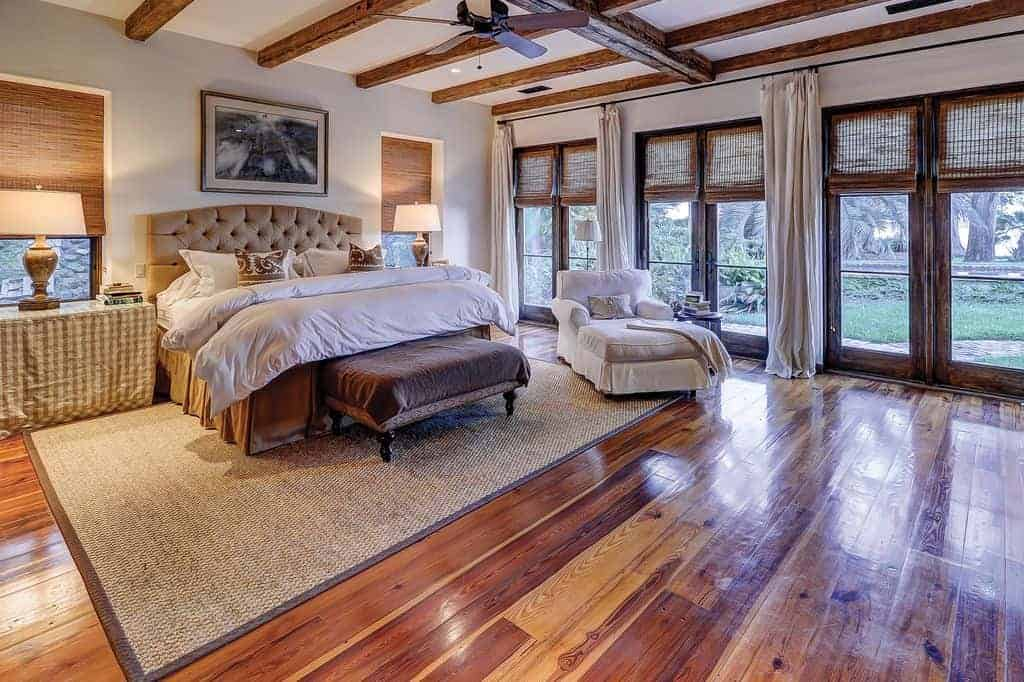 A very cozy room with wood beam ceiling and French doors covered in wicker roman shades. It offers a chaise lounge and a beige tufted bed that sits on a jute area rug over the wide plank flooring.