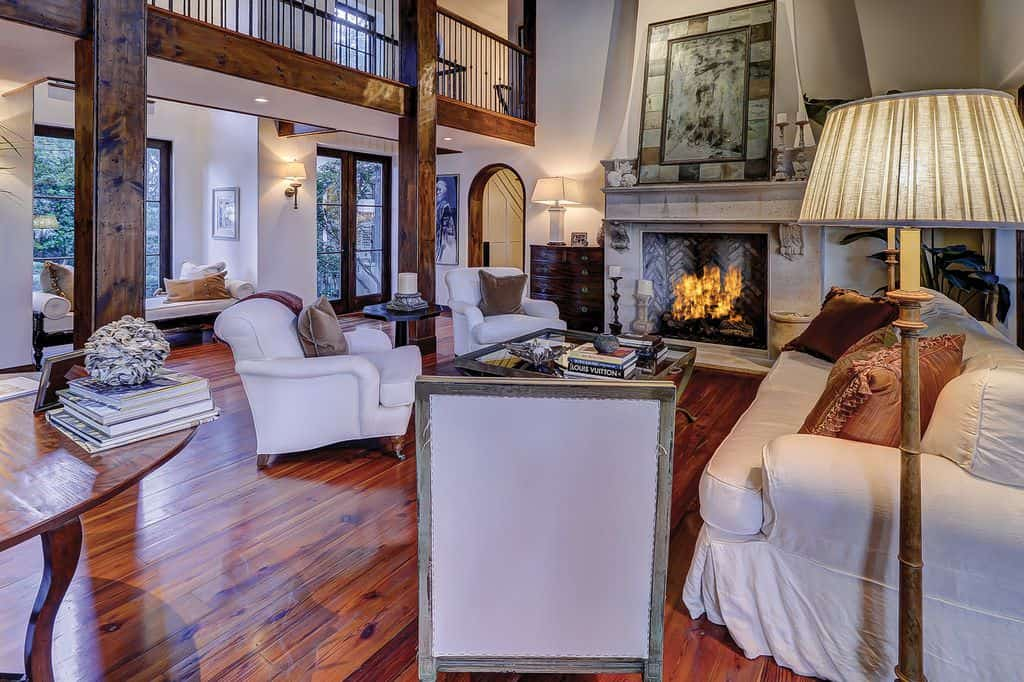 Large living room with white furniture, rich wood flooring, upper landing looking down and tall ceiling. Beautiful.