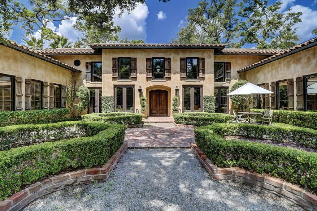 Exterior front entrance to Tuscan style mansion with box hedges leading up to the front door.